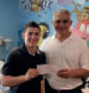 Chris Norton presents a check from his fundraisers